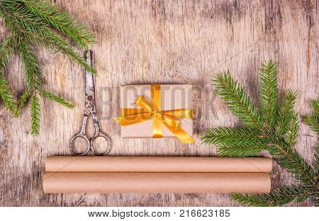 Christmas decorations with fir tree and gift box. Preparation for Christmas gift wrapping. Vintage scissors and packing paper.