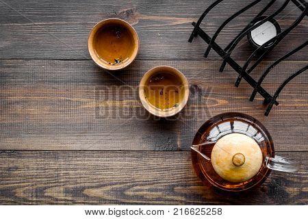 Tea break. Cookware fo tea ceremony. Tea pot and cups on dark wooden background top view.