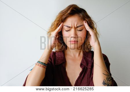 Portrait of tired young Asian woman wearing shirt having headache touching her head. Annoyance and stress concept