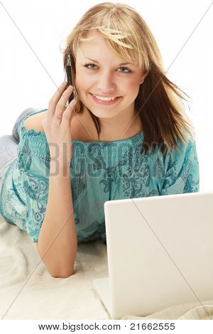 Happy beautiful woman talking on mobile phone in front of the laptop