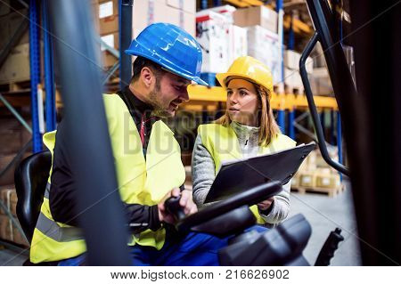 Young warehouse workers working together. Man sitting in a forklift and woman holding notes, discussing something.