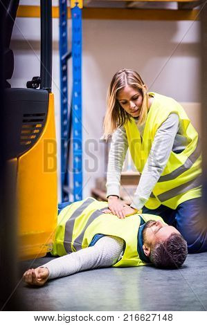 An accident in a warehouse. Woman performing cardiopulmonary resuscitation.