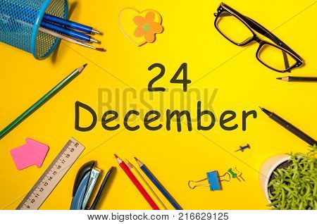 Eve. December 24th. Day 24 of december month. Calendar on yellow businessman workplace background. Winter time.