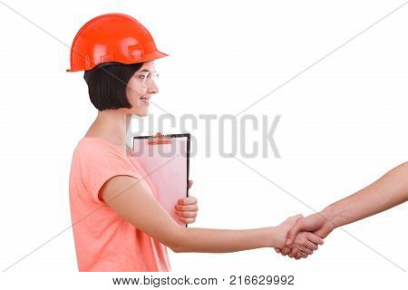 A beautiful girl with a smile in a helmet contractor shakes hands on a white isolated background