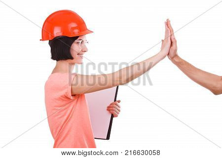 A girl with a smile in a hard hat and glasses, with a tablet in hand a contractor gives five and looks directly on a white isolated background