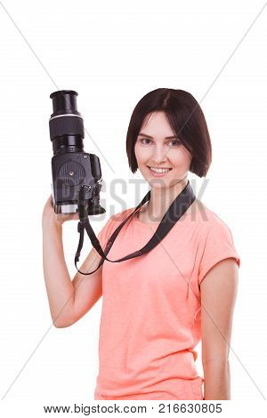 Young brunette girl in pink t-shirt holds camera in hand and looks to the side on white isolated background