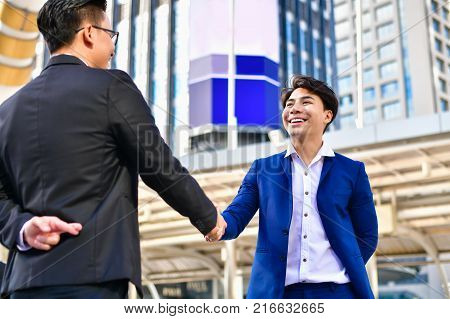 Business concept hypocrisy Young businessmen shake hands with fraudulent models.