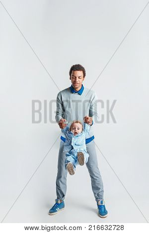 A happy family of afro man and caucasian child on white studio background