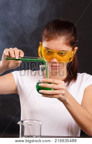 The girl the laboratory assistant young, in a white tank top, in glasses. Pouring green liquid from a test tube into a test tube into a flask on a black background
