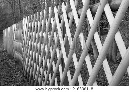 Criss cross lines of a wooden fence reaching to the distance