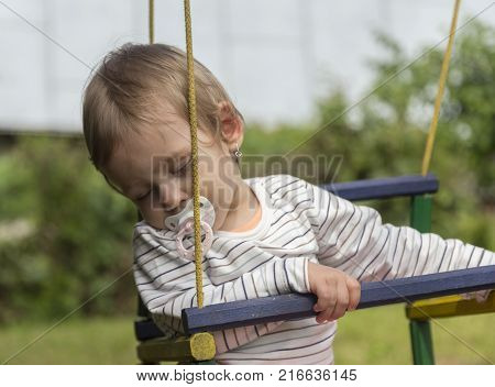 An older sister is swinging her two younger sister twins on a swing