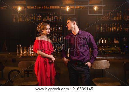 Acquaintance in bar, woman flirts with man
