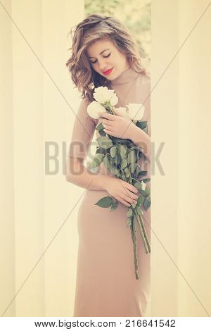 beautiful woman with a bouquet of roses standing near ancient colons
