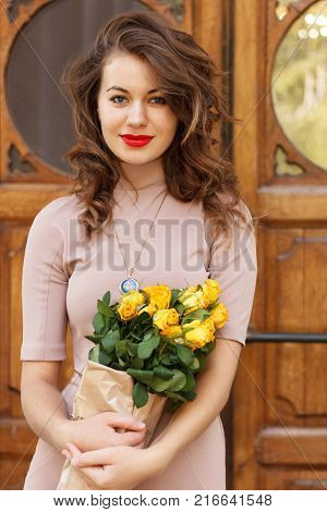 Portrait of beautiful woman with yellow roses standing near an ancient wooden door