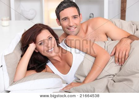 a couple reposing in bed in the morning
