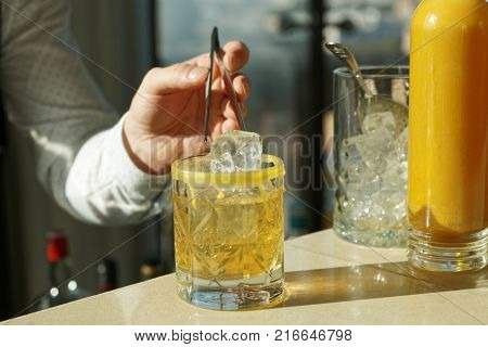 Barman is adding an ice cube to the cocktail with pincers