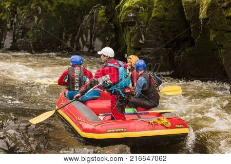 Llangollen Wales UK - January 28 2017: White water rafters negotiating the Serpents Tail a narrow gorge on the River Dee in North Wales