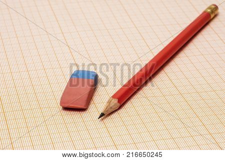 On the millimeter paper lie an eraser and a simple pencil close-up