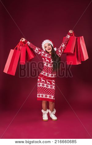 Young pretty woman or girl with long beautiful hair in Santa hat and New Year's dress holding red package on red studio background. Christmas sale. Emotional brunette. Copy space. Full-length photo