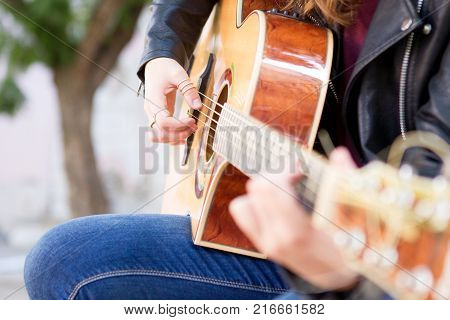 Closeup of acoustic guitar and woman hands on strings. Music and creative concept