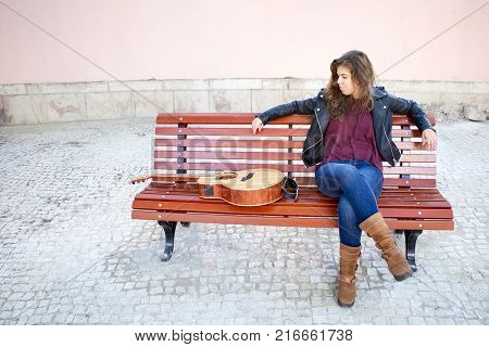 Pensive female street musician sitting on bench, looking at her guitar in minute before start playing. Creative work concept