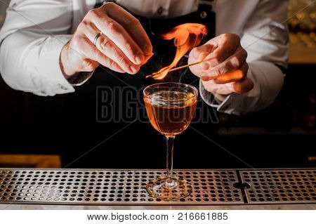 Bartender in white shirt making a fresh burning cocktail with a smoky note on the bar counter
