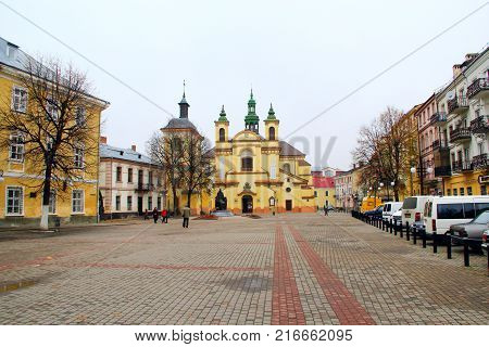 Ivano-Frankivsk / Ukraine - 29 October 2017 / Ukraine: Ivano-Frankivsk city views: walking area with a view of the Church of Vir gin Mary. 29 October 2017 Ivano-Frankivsk, Ukraine.