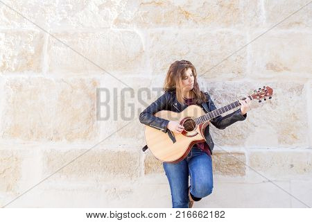 Portrait of thoughtful young female street musician playing guitar with granite wall in background. Creativity concept.