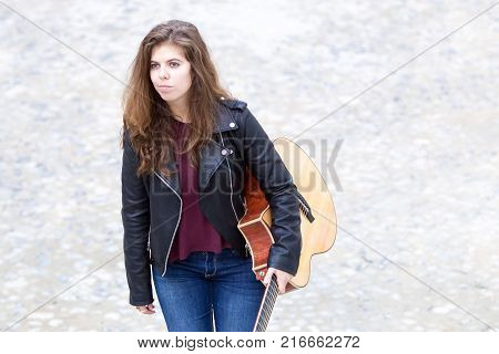 Portrait of serious young woman standing in street and holding acoustic guitar in arm. Creative work concept