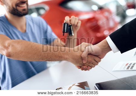 A man buys a new car in a light large car showroom. There are many modern cars.