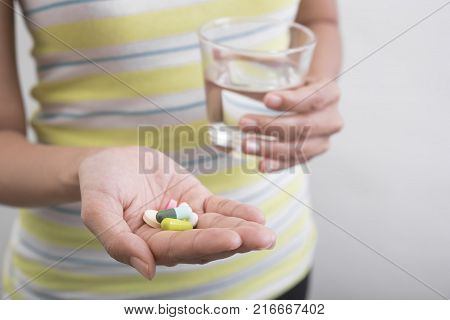 women hand holding glass of water are taking medicine for healthy.