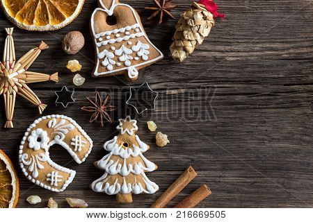 Christmas background with copy space: decorated gingerbread cookies straw ornaments star anise nutmeg cinnamon frankincense resin and dried orange slices on a wooden background