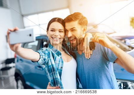 A young family came to the car showroom to choose a new car. They are very happy about this, they are in a good mood. There are many modern cars.