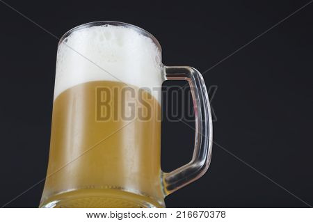 A glass of beer on a dark background with space for text. A mug of beer with foam. A glass of cold beer close up. A glass of unfiltered beer with condensation. The swirling mug of light beer.