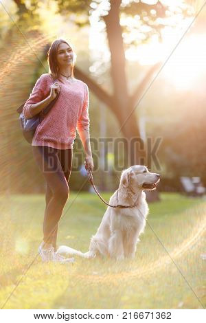 Picture of young brunette on walk with dog in summer park at lawn. Lensflare effect