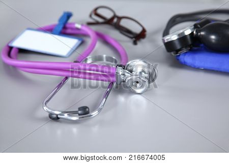 stethoscope, Red heart, glasses and blood pressure meter on white background. Selective focus