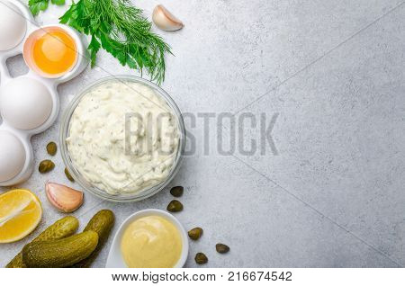 Homemade white sauce tartar tartare with ingredients pickles, capers, dill, parsley, garlic, lemon and mustard on a light stone background. Horizontal, copy space, top view