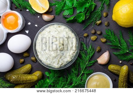 Homemade white sauce tartar tartare with ingredients pickles, capers, dill, parsley, garlic, lemon and mustard on a dark black stone concrete background. Horizontal, top view