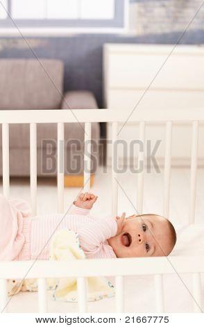 Cute baby girl wearing pink lying in white crib.?