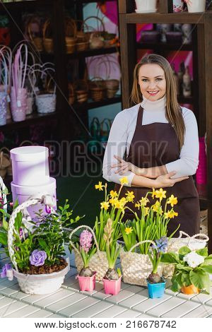 seller of a flower shop, standing next to the table with flowers, crossed her hands and smiling, looking at the camera
