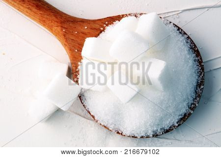 Cubes of sugar and granulated sugar with wooden spoon.