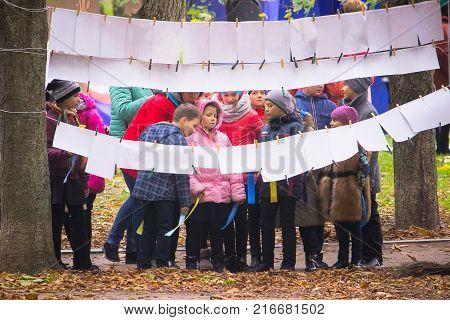 Zhytomyr Ukraine - October 19 2015: Kids watching photos on the street at autumn park