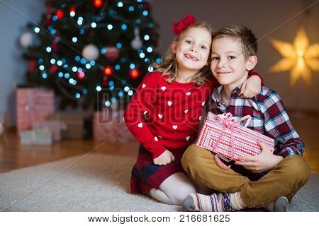 Two Happy Children In New Year Eve With Presents Near New Year Tree