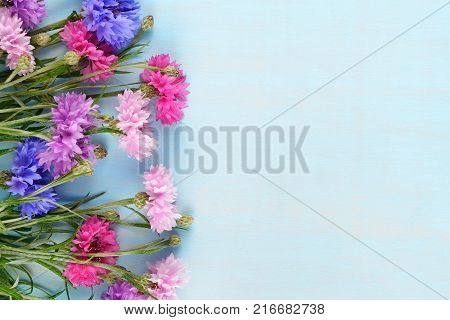 Cornflowers on blue table top view with copy-space