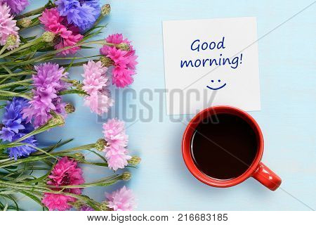 Good morning wishes coffee cup and cornflowers on blue background top view