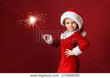 Christmas, x-mas, winter, happiness concept - smiling little girl in Santa Claus dress with sparkler