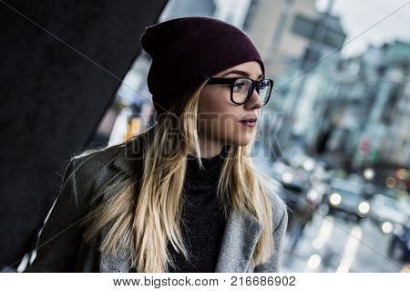 She is trendy girl. Portrait of stylish blonde woman in eyeglasses looking away while standing outdoors. Fashionable hipster girl in gray coat walking city streets. Autumn city fashion.