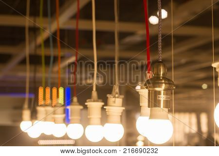 multiple LED lamps SUN lights and hang in a row on the long cords of different colors. simple light bulbs technology background conceptual