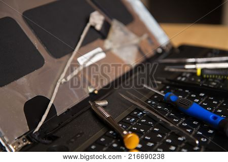 laptop on the keyboard are repair tools tweezers screwdriver and dismantled the display. Repair of computer equipment. Repair services innovative technology.