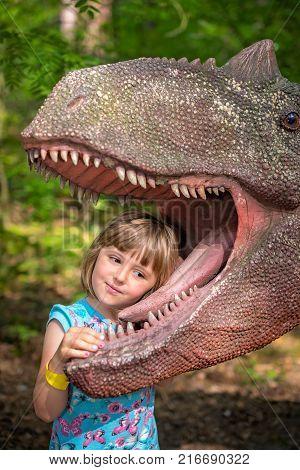 Little girls head in the mouth a dinosaur replica in an amusement park